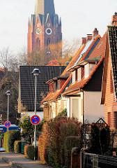 Einzelhäuser in einer Wohnstrasse in Buxtehude - im Hintergrund der Kirchturm der St. Petrikirche.