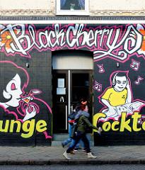 Hausfassade mit Graffiti - Bar; Fussgänger - Bilder aus der Stadt Uetersen, Kreis Pinneberg.
