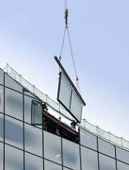 Fassade der Hamburger Elbphilharmonie wird geschlossen - ein Kran passt das Fensterelement in die Fassade ein.