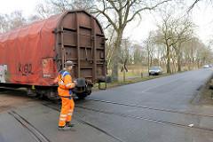 Ein Güterzug überquert die Strasse Grosse Twiete in Uetersen - ein Bahnmitarbeiter sichert die Strecke.