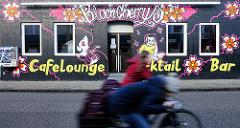 Bunte Hausfassade / Graffiti - Werbung eines Cafes, Cocktail-Bar; Radfahrer auf der Strasse - Bilder aus der Stadt Uetersen, Kreis Pinneberg.