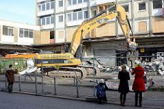 Der Abriss bei den Esso-Häusern hat begonnen - die legendäre Tankestelle auf dem Hamburger Kiez an der Reeperbahn wurde am 12.02.14 abgerissen; ein Bagger räumt die Metallteile in Container. Anwohner beobachten und fotografieren das Ereignis.