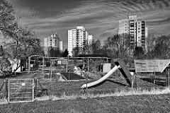 Schrebergärten mit Kinderrutsche - im Hintergrund die Hochhäuser am Finkenbrook in Uetersen, Kreis Pinneberg; schwarz-weiss Fotografie.