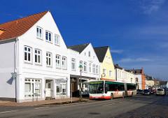Wohnhäuser, Geschäftshäuser in der Marktstrasse von Uetersen - Bushaltestelle; weisse Fassaden, blauer Himmel.