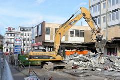 Der Abriss bei den Esso-Häusern hat begonnen - die legendäre Tankestelle auf dem Hamburger Kiez an der Reeperbahn wurde am 12.02.14 abgerissen; ein Bagger räumt die Metallteile in Container.