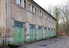 Nebengebäude beim Marstall von Ludwigslust - denkmalgeschützte Architektur; Garagen mit Holztoren.