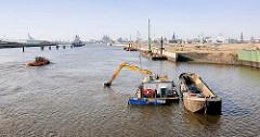 Baggerarbeiten in der Norderelbe - Elbvertiefung; ein Bagger hebt Schlamm vom Flussgrund und füllt den Schlick in eine Schute - im Hintergrund der Kirchenpauerkai in der Hamburger Hafencity.