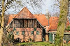 Historische Architektur auf dem Klosterhof in Uetersen - Fachwerkgebäude mit Holzfassade; im Hintergrund der Kirchturm der Klosterkirche.