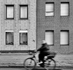 Klinkerfassade - Fenster; Radfahrer in Fahrt; Schwarz-Weiss Foto / Bilder aus der Stadt Uetersen, Kreis Pinneberg.