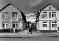 Einzelhäuser mit unterschiedlicher Fassadengestaltung - Fussgänger; Bilder aus Uetersen - Metropolregion Hamburg / Schwarz-Weiss Fotografie.
