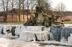 Skulpturenschmuck der Grossen Kaskade am Schlossplatz von Ludwigslust - Allegorien auf die Flüsse Stör und Rögnitz. Winterbilder - gefrorenes fliessendes Wasser. Im Hintergrund das barock-klassizistische Prinzenpalais.