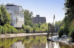 Industriegebäude / Gewerbegebäude am Ufer der Pinnau in Uetersen - Niedrigwasser auf dem Fluss / rechts eine Steuerbordpricke - Fahrwasserkennzeichnung, am oberen Ende zusammengebundene Zweige auf einer Stange.