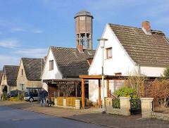 Einzelhäuser mit Spitzdach in der Birkenalle von Uetersen im Kreis Pinneberg - im Hintergrund der Wasserturm.