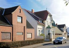 Unterschiedliche Architekturstile - Wohnhäuser in Uetersen; Jugendstilvilla und Wohnhaus mit Klinkerfassade - geschlossene Jalousie vor dem Fenster.