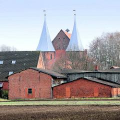 Landwirtschaftliche Nutzgebäude - Scheunen am Feld; dahinter die Türme vom Dom zu Bardowick St. Peter Paul.  Die gotische dreischiffige Hallenkirche, erbaut zwischen 1389 und 1485.