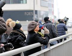 Presse und Passanten beobachten die Arbeiten an der Fassade der Elbphilharmonie von der Mahatma-Gandhi-Brücke aus.