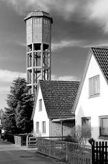 Wasserturm in Uetersen - Einzelhäuser mit Spitzdach; der 1926 errichtete 39m hohe Wasserturm steht unter Denkmalschutz - zylindrischer Wasserbehälter mit Ziegelmauerwerk verkleidet - Stahlbeton-Skelettkonstruktion.