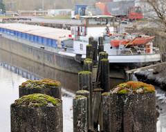 Binnenschiffe am Kai an der Pinnau in Uetersen - Eisendalben mit Moos bewachsen.