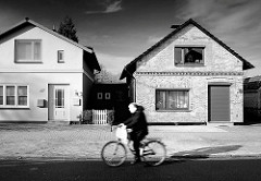 Wohnhäuser - Einzelhaus, unterschiedliche Fassadengestaltung / Klinkerfassade, Ziegelfassade + glatt verputzte Hausfassade - Radfahrer in Fahrt, Schwarz-Weiss Darstellung.