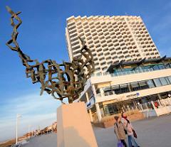 Bronzeplastik Möwenflug an der Strandpromenade im Ostseebad Warnemünde; Bildhauer Reinhard Dietrich - im Hintergrund das Hotelhochhaus Neptun.