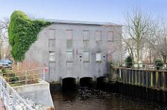 Ruine Industrieachitektur - Mühlengebäude über der Krükau in Elmshorn - die Fenster sind mit Holzplatten vernagelt.