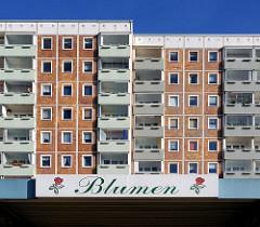 Hochhäuser / Wohnhaus, Plattenbau - Hansestadt Rostock, Ortsteil Lichtenhagen. Hausfassade mit Balkons, Schild Blumen.