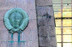 Bronzerelief sowjetisches Staatswappen - Ehrenmal für sowjetische Soldaten / Neuer Markt, Hansestadt Stralsund - errichtet 1967. Im Hintergrund Kirchenfenster der St. Marienkirche.