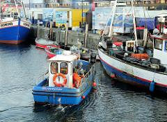 Fischerboote im Hafen von Warnemünde - ein Motorboot legt an der Kaimauer an.