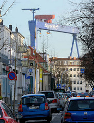 Strasse mit mehrstöckigen Wohnhäusern in Warnemünde, Strassenverkehr - Hafenkran, Werftkran der Warnow Werft.