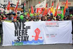 Demonstration für das Bleiberecht der Lampedusa-Flüchtlinge in Hamburg - Demonstranten, Fahnen; Transparent WE ARE HERE TO STAY, Solidarität mit Lampedusa in Hamburg.