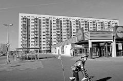 Supermarkt und Plattenbau, mehrstöckiges Wohnhaus in Rostock Lichtenhagen - Schwarz Weiss Aufnahme.