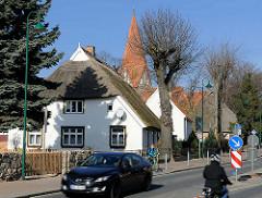 Dorfstrasse mit reetgedeckten Häuser in Elmenhorst / Lichtenhagen, Landkreis Rostock - im Hintergrund der Kirchturm der Dorfkirche Lichtenhagen.