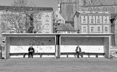Bushaltestelle mit Graffiti - im Hintergrund Wohnhäuser und das Kirchenschiff der St. Marienkirche in der Hansestadt Stralsund.