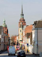 Strasse mit Wohngebäude / Geschäftshäusern in Itzehoe - Kirchturm der St. Laurentii Kirche.