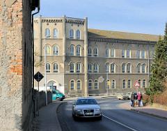 Historisches Kasernengebäude / Westkaserne des 9. Ulanenregiments / ehem. Kreiskrankenhaus der Hansestadt Demmin; Mauer mit abbröckelnden Putz, Ziegelsteine.