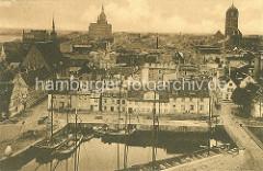 Historische Luftansicht vom Hafen der Hansestadt Stralsund  - Segelschiffe an der Kaimauer; lks. die Heiliggeistkirche; re. davon die St. Marienkirche und re. der Kirchturm der St. Jakobi Kirche.