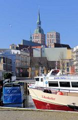 Fahrgastschiffe im Hafen der Hansestadt Stralsund - Schild Frischfisch und Räucherfisch - im Hintergrund die Kirchtürme der St. Nikolaikirche.
