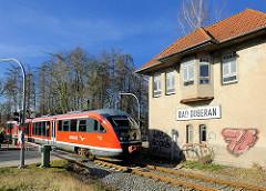 Schrankenhäuschen Bad Doberan - roter REGIO Zug der Deutschen Bahn.