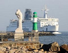 Mole mit Leuchtfeuer bei Warnemünde an der Ostsee - Scandlines Fähre Kronprins Frederik läuft in die Warnow ein - lks. Skulptur Grosse Stehende, trauernde Seemannsfrau, Bildhauer Werner Stölzer.