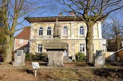 Sogen. Neunerdenkmal in Itzehoe - Ehren und Mahnmal für die im 1. Weltkrieg gefallenen 378 Soldaten des Feldartellerieregiments Nr. 9. Im Hintergrund das Probstenhaus / Hauptpastorat.