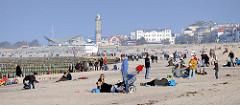 Sandstrand im Ostseebad Warnemünde - Touristen am Strand in der Sonne - im Hintergrund Häuser und der Leuchtturm von Warnemünde.