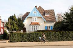 Einzelhaus, Stadtvilla - blauer Holzgiebel; Fahrradfahrerin in Fahrt.