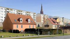 Wohngebäude in der Hansestadt Demmin - Doppelhäuser mit Vorgarten, mehrstöckige Wohnblocks; Spitze des Kirchturms der St. Bartholomaei Kirche.