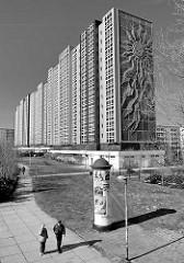 Architektur in Rostock Lichtenhagen - Plattenbau, Hochhaus mit Sonnenblumen Relief als Hausfassade; Litfaßsäule / Fussgänger - Schwarz Weiss Motiv.