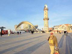Strandpromenade in Warnemünde; Abendsonne, lange Schatten - Leuchtturm Seebad Warnemünde, erbaut 1898 / Höhe 36,90m - sogen. Teepott Warnemünde, erbaut 1967- Hyparschalenarchitektur, Mehrzweckhalle - Architekt Ulrich Müther.