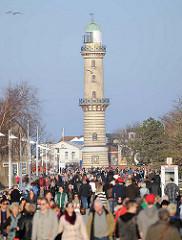 Strandpromenade / Flaniermeile im Ostseebad Warnemünde - Touristen in der Sonne; historischer Leuchtturm, erbaut 1898.
