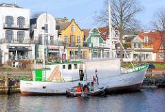 Fischerboot im Hafen von Warnemünde / Alter Strom - historische Architketur, Wohnhäuser an der Promenade vom Seebad Warnemünde.