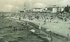 Historisches Motiv Strandleben in Warnemünde - im Hintergrund Häuser und Leuchtturm - Touristen am Strand, Strandkörbe.