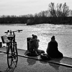 Picknick im Hafen von Itzehoe - zwei Frauen sitzen auf der Kaimauer an der Stör und essen ein Sandwich / Gegenlichtaufnahme, schwarz-weiss.