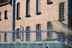 Justizvollzugsanstalt Itzehoe - rotes Backsteingebäude, erbaut 1876 - vergitterte Fenster - Mauer mit Stacheldrahtrolle, Natodraht.
